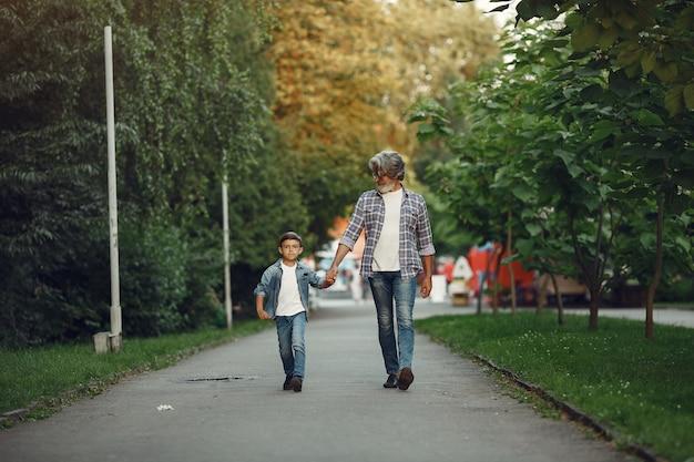 Chłopiec i dziadek spacerują po parku. stary człowiek gra z wnukiem.