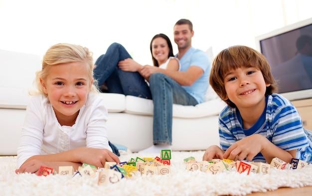 Chłopiec i dziewczyna bawić się z abecadło sześcianami w domu