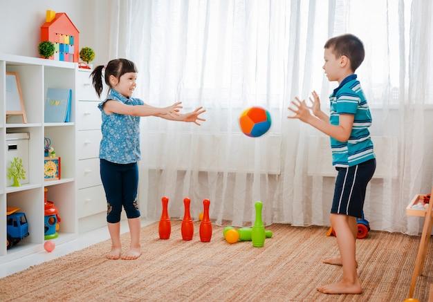 Chłopiec i dziewczynka bawi się piłką w pokoju gier dla dzieci