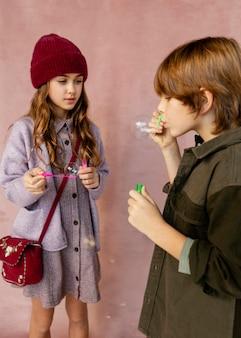 Chłopiec i dziewczynka bawić się bańkami mydlanymi