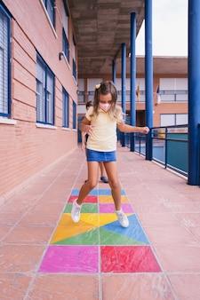 Chłopiec i dziewczynka biegają i skaczą na boisku szkolnym z maską podczas pandemii covid. powrót do szkoły podczas pandemii covid