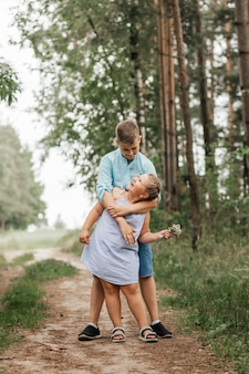 Chłopiec i dziewczynka, brat i siostra w naturze latem przytulanie i granie