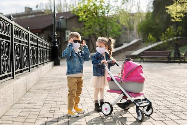 Chłopiec i dziewczynka chodzą z wózkiem w ochronnych maskach na twarz. pojęcie rodziny. koronawirus (covid-19