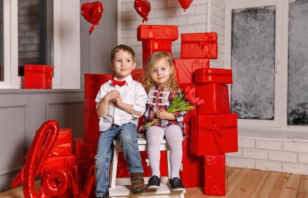 Chłopiec i dziewczynka dają prezent na walentynki, przytulanie młodej pary