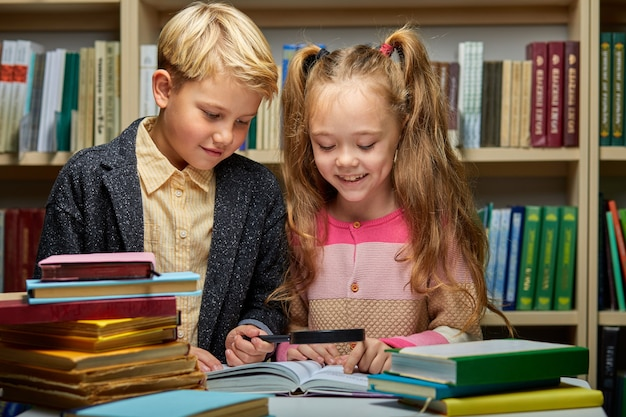 Chłopiec i dziewczynka dzieci, czytanie książek w bibliotece, styl życia ludzi i koncepcja edukacji. młoda przyjaźń i związek dzieci w koncepcji szkoły