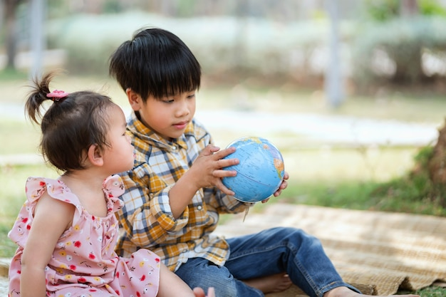 Chłopiec i dziewczynka dzieci patrząc na świecie do nauki mapy świata