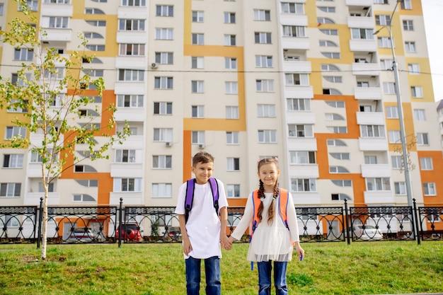 Chłopiec i dziewczynka idą do szkoły za rękę na tle elewacji nowego budynku