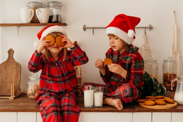 Chłopiec i dziewczynka jedzą świąteczne ciasteczka i piją mleko