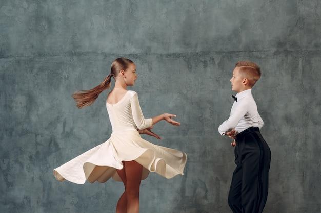 Chłopiec i dziewczynka młodych tancerzy tańczy w tańcu towarzyskim samba.