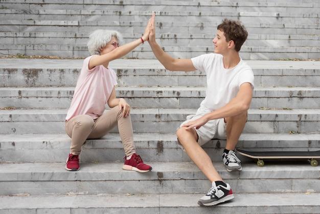 Chłopiec i dziewczynka przybijają piątkę siedząc na schodach