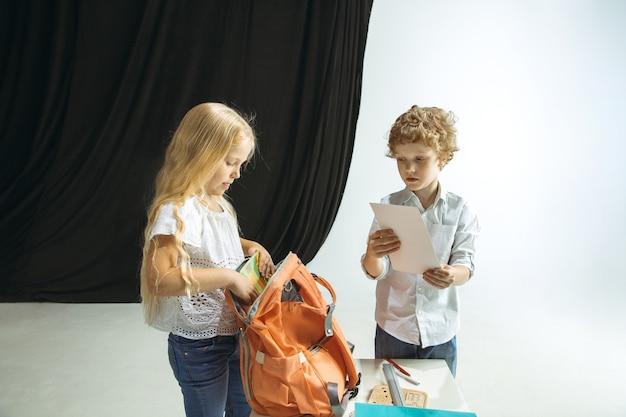 Chłopiec i dziewczynka przygotowują się do szkoły po długiej letniej przerwie. powrót do szkoły. małe modele kaukaski pakowanie torby razem na tle studio. koncepcja dzieciństwa, edukacji, wakacji lub pracy domowej.