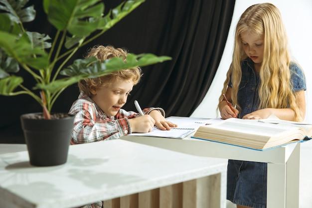 Chłopiec i dziewczynka przygotowują się do szkoły po długiej letniej przerwie. powrót do szkoły. małe modele kaukaski razem odrabiania lekcji na tle studio. koncepcja dzieciństwa, edukacji, wakacji lub pracy domowej.