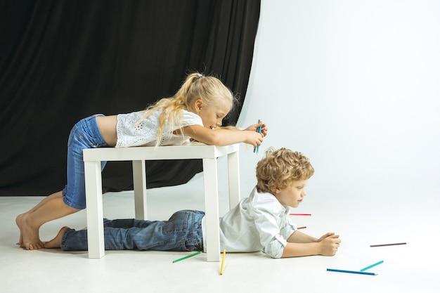 Chłopiec i dziewczynka przygotowują się do szkoły po długiej przerwie letniej. powrót do szkoły. małe kaukaski modele bawiące się razem w przestrzeni