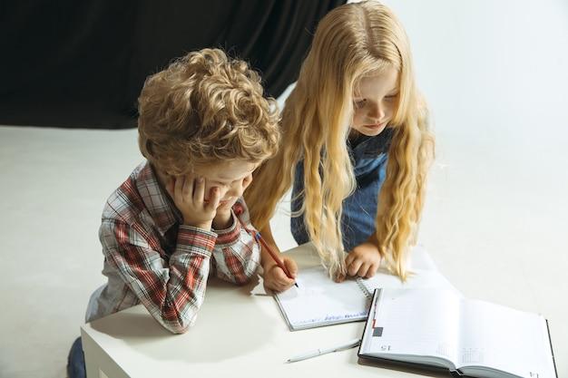 Chłopiec i dziewczynka przygotowują się do szkoły po długiej przerwie letniej