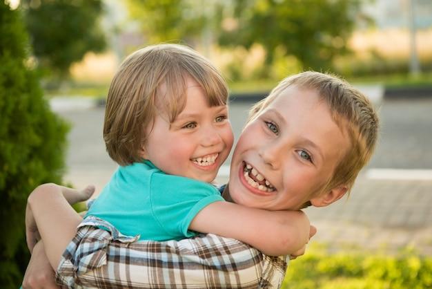 Chłopiec i dziewczynka przytulanie. zielona łąka śmieszne dzieci.