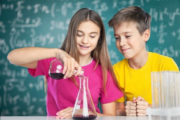 Chłopiec i dziewczynka robi eksperyment chemiczny. wlewanie płynu do zlewki