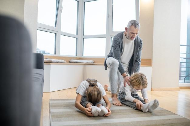 Chłopiec i dziewczynka robią rozgrzewkę na podłodze i tata