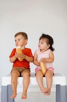 Chłopiec i dziewczynka siedzi na stole i jedzenie chleba