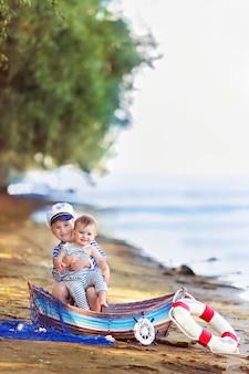Chłopiec i dziewczynka siedzi w łodzi, przebrany za marynarza, na piaszczystej plaży z muszelkami nad morzem