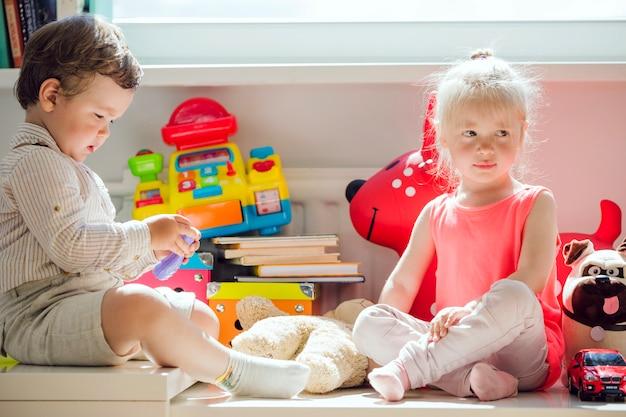 Chłopiec i dziewczynka siedzi w oknie stwarzających