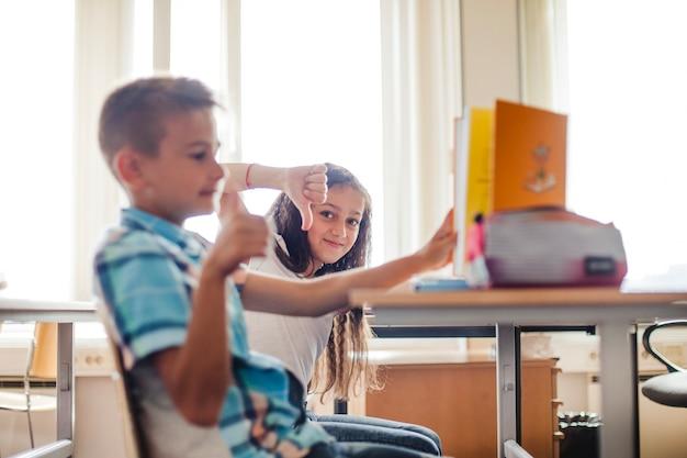 Chłopiec i dziewczynka siedzi w szkole biurko