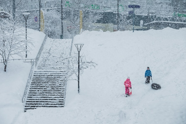 Chłopiec i dziewczynka śnieżne tuby podczas opadów śniegu