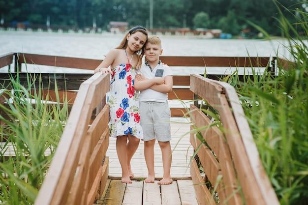 Chłopiec i dziewczynka stojąc na drewnianym molo na brzegu jeziora. letnie wakacje