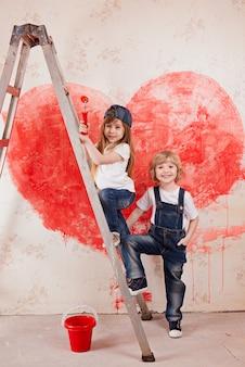 Chłopiec i dziewczynka w dżinsach i białej koszuli, z pędzlem i stojakiem na wiadro na drabinie malują ścianę