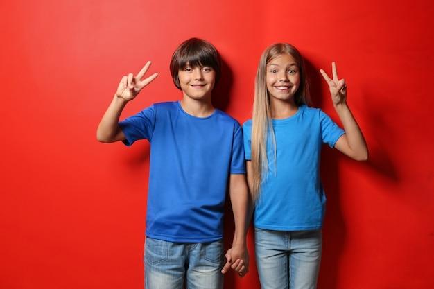 Chłopiec i dziewczynka w koszulkach pokazujących gest zwycięstwa na kolorze