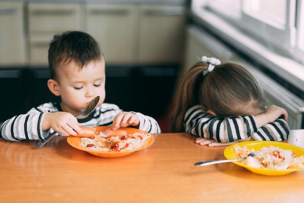 Chłopiec i dziewczynka w kuchni jedzący makaron są bardzo głodni, dziewczyna nie lubi tego zdenerwowana
