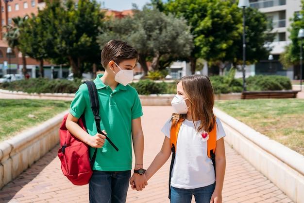 Chłopiec i dziewczynka z plecakami i maskami idzie do szkoły w pandemii koronawirusa