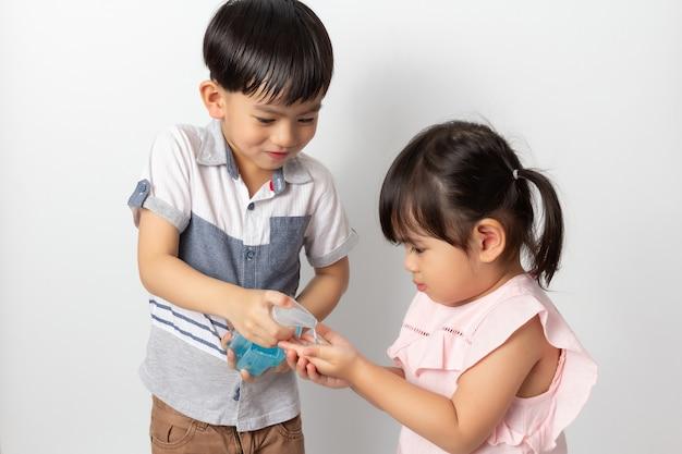 Chłopiec i dziewczynka za pomocą alkoholu żel antyseptyczny do czyszczenia rąk. dezynfekcja koronawirusem
