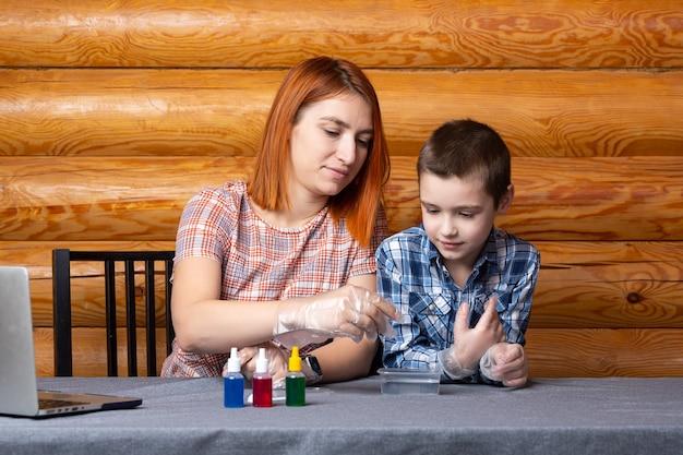 Chłopiec i jego matka naukowcy wlewają mieszaninę z probówki do pojemnika