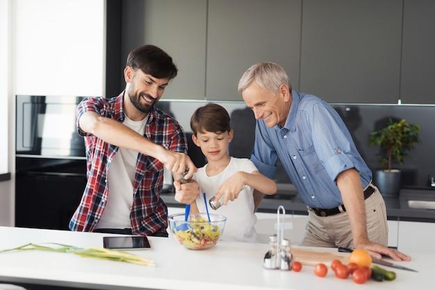 Chłopiec i jego ojciec dodają przyprawy do prawie gotowej sałatki.