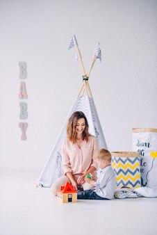 Chłopiec i jego piękna młoda matka bawi się wraz z zabawkami edukacyjnymi w jasnym pokoju z dziecięcym wigwamem i eko-torbami na zabawki.