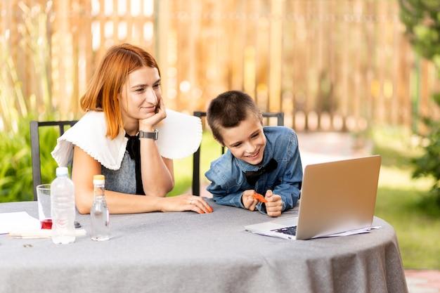 Chłopiec i matka wychodzą na wykład, używają laptopa i komunikują się przez internet w domu. nauczanie domowe, nauczanie na odległość, online e