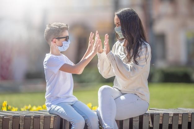Chłopiec i młoda kobieta przybijają piątkę obiema rękami, siedząc na zewnątrz, nosząc maski na twarz.