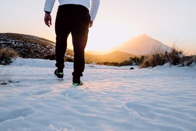 Chłopiec idąc przez śnieg podczas zachodu słońca