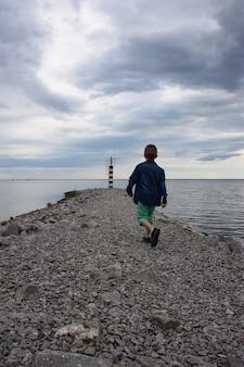 Chłopiec idący plecami w kierunku latarni wzdłuż pomostu z kamieni