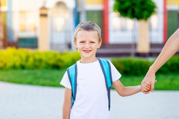 Chłopiec idzie z plecakiem do szkoły lub przedszkola za rękę z mamą-rodzicem i uśmiecha się, pomysł wraca do szkoły