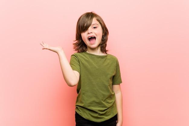 Chłopiec imponujący mienie kopii przestrzeń na palmie.