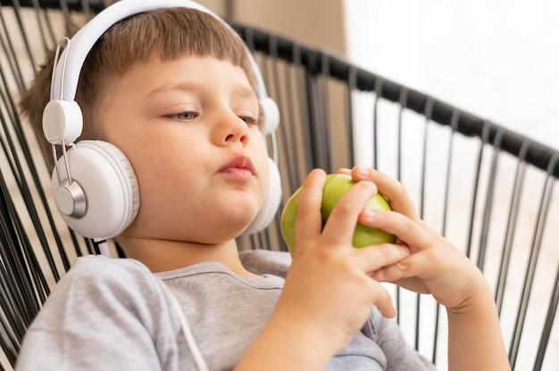 Chłopiec je jabłka z hełmofonami