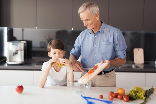 Chłopiec je kanapkę z sałatką.