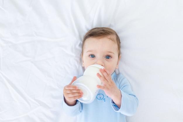 Chłopiec je mleko z butelki na łóżku przed pójściem spać w niebieskim body, koncepcja żywności dla niemowląt