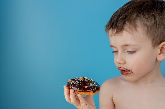 Chłopiec je pączek czekoladę. śliczny szczęśliwy chłopiec posmarowany czekoladą wokół ust. koncepcja dziecka, smaczne jedzenie dla dzieci