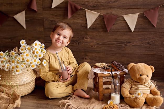 Chłopiec je pączki i pije mleko ze słomy. świetne jedzenie dla dzieci.