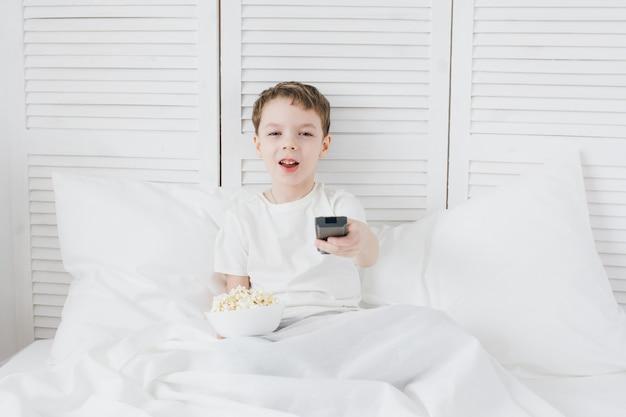 Chłopiec je popkornu obsiadanie w łóżku i ogląda tv