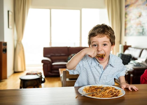 Chłopiec je spaghetti
