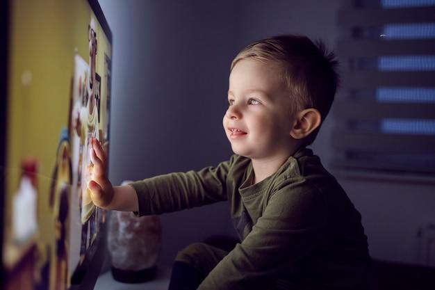Chłopiec jedną ręką dotknął ekranu telewizora