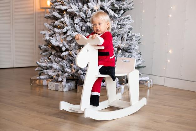 Chłopiec jedzie na koniu zabawkowym w pobliżu choinki w świątecznie urządzonym domu